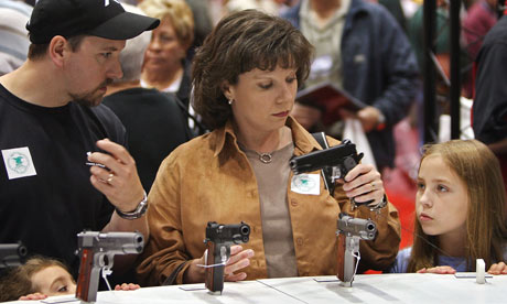 A family with 2 daughters looks at a pistol at the National Rifle Association Convention