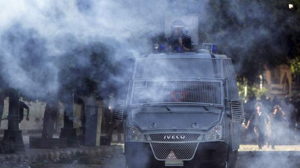 Riot policemen throw stones and release tear gas during clashes with protesters along a road which leads to the U.S. embassy, near Tahrir Square in Cairo