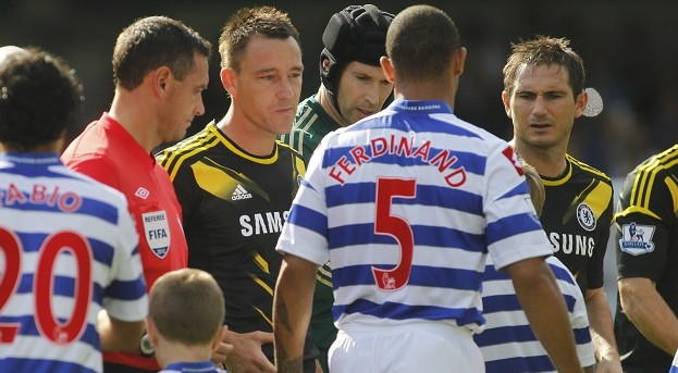 Queens Park Rangers' Anton Ferdinand ignores the hand of Chelsea's John Terry, third left, during a pre-match handshakes before the start of their English Premier League soccer match at Loftus Road stadium, London, Saturday, Sept. 15, 2012. Chelsea's captain John Terry was acquitted in July of racially abusing Anton Ferdinand in last year's corresponding match.