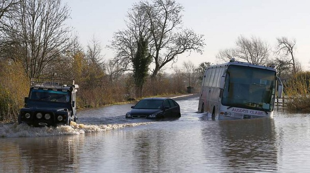 A Land Rover is driven past a car and bus stranded in flood waters from the River Soar near Mountsorrel, central England November 23, 2012.
