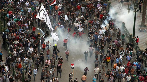 Protesters demonstrating against Egypt's Islamist President Mohamed Morsi run from tear gas fired by Egyptian riot police during clashes in Cairo's landmark Tahrir square on November 23, 2012. Morsi has assumed temporary sweeping powers that supporters say will cut back a turbulent and seemingly endless transition to democracy, but outraged critics say he has now become a dictator.