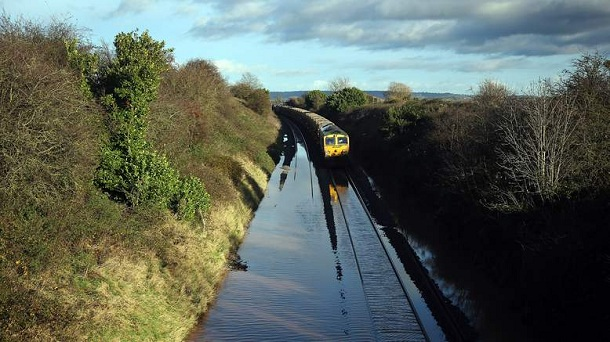 TAUNTON, ENGLAND - NOVEMBER 21:  A train waits to pass along flooded track close to the village of North Curry on November 21, 2012 near Taunton, England. Heavy rain overnight has brought widespread disruption to many parts of the UK particularly in the Somerset and Wiltshire and weather forecasters have warned of more wet and windy weather to come.