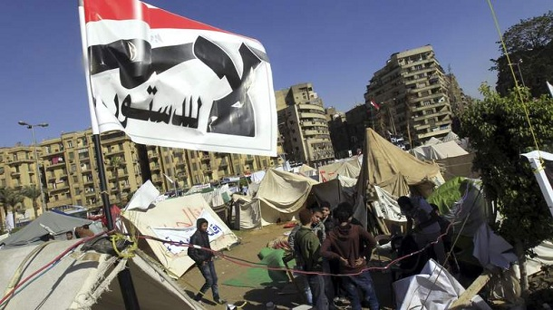 """Anti-Mursi protesters sit outside their tents, below a flag that reads, """"No, to Constitution"""" at Tahrir Square in Cairo December 10, 2012. The Egyptian government has given the military the authority to arrest civilians to help safeguard a constitutional referendum Islamist President Mohamed Mursi has planned for Saturday, the official gazette said."""