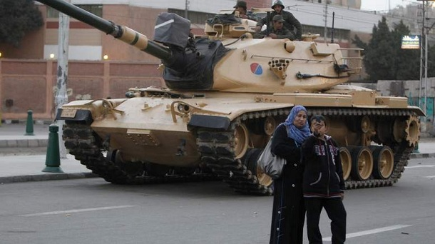 An Egyptian boy and his mother take a photo near an army tank from the republican guard in front of the presidential palace in Cairo December 10, 2012. Egypt's Islamist President Mohamed Mursi has given the army temporary power  to arrest civilians during a constitutional referendum he is determined to push through despite the risk of bloodshed between his supporters and opponents accusing him of a power grab.