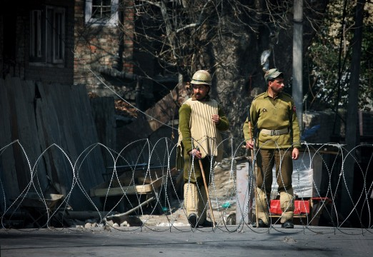 Policemen enforce curfew in Indian Kashmir.