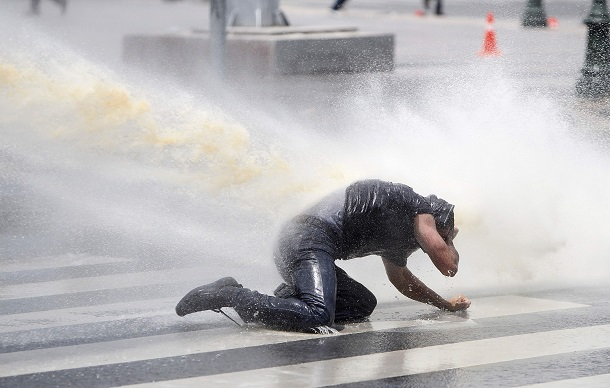 Protester is being sprayed by the police's water cannon during a demonstration at Kizilay square in central Ankara